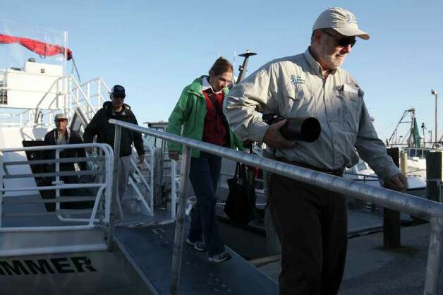 The Aransas Project Director Ron Outen, right, disembarks in Fulton, Texas after a whooping crane tour in the Aransas National Wildlife Refuge, Tuesday, Nov. 29, 2011. The Aransas Project is suing officials with the Texas Commission on Environmental Quality for what they content is a failure to control the flow of fresh water from the rivers that empty into the refuges that contributed to the death of whooping cranes between 2008-2009. With the ongoing drought and low river water flow, high salinity in the waters of the bay caused a bloom of red tide that lead to the closing of the oyster season and the decline in blue crabs. The crabs are the main source of food for the cranes. Photo: JERRY LARA, Jerry Lara/glara@express-news.net / SAN ANTONIO EXPRESS-NEWS