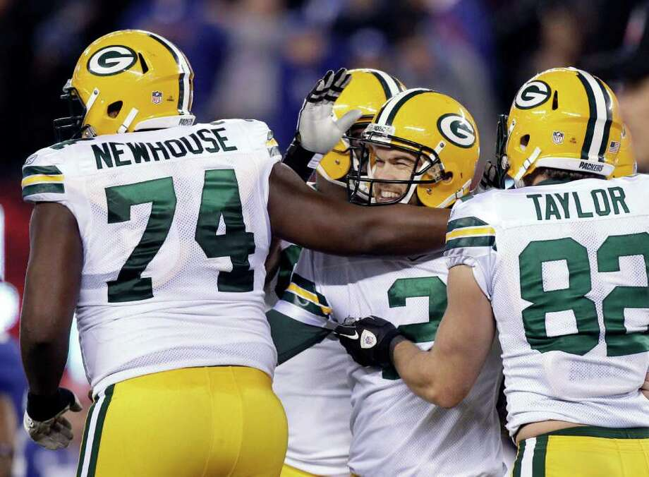 Mason Crosby (center) is congratulated by teammates after nailing a 31-yard field goal to help Green Bay rally. Photo: AP