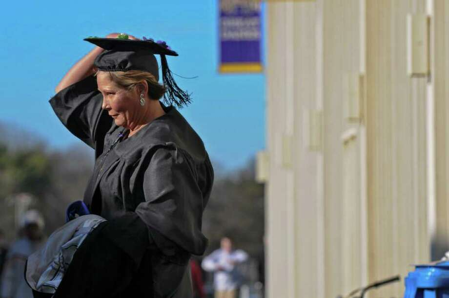 A UAlbany graduate holds onto her mortarboard as she proceeds  through the wind from the physical education building and into the adjacent SEFCU Arena for  the Winter Commencement  on Sunday Dec. 4, 2011 in Albany, NY. (Philip Kamrass / Times Union ) Photo: Philip Kamrass / 00015597A