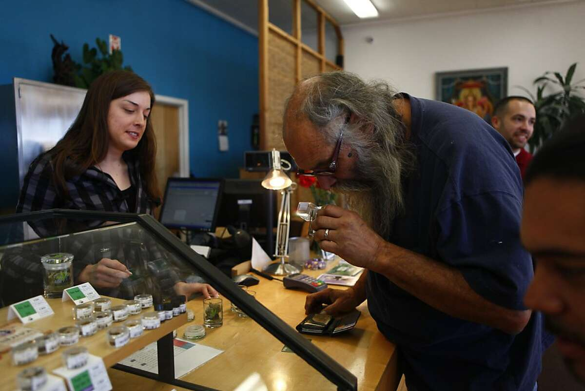 Norman Fahmie (right) of El Sobrante inspects some medical cannabis from the display case as Elyse Jones (left) sales staff helps him at the smokables, edibles, concentrates and seeds counter at the Harborside Health Center on Wednesday, November 30, 2011 in Oakland, Calif.