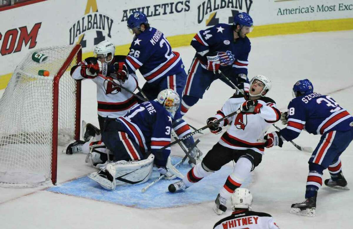 Rochester Americans goalie Drew MacIntyre is surrounded by teammates and Albany Devils players Steve Zalewski, left, and Steve Bernier, right, as the net comes off the posts during the first period of a game at the Times Union Center on Sunday Dec. 4, 2011 in Albany, NY. (Philip Kamrass / Times Union )