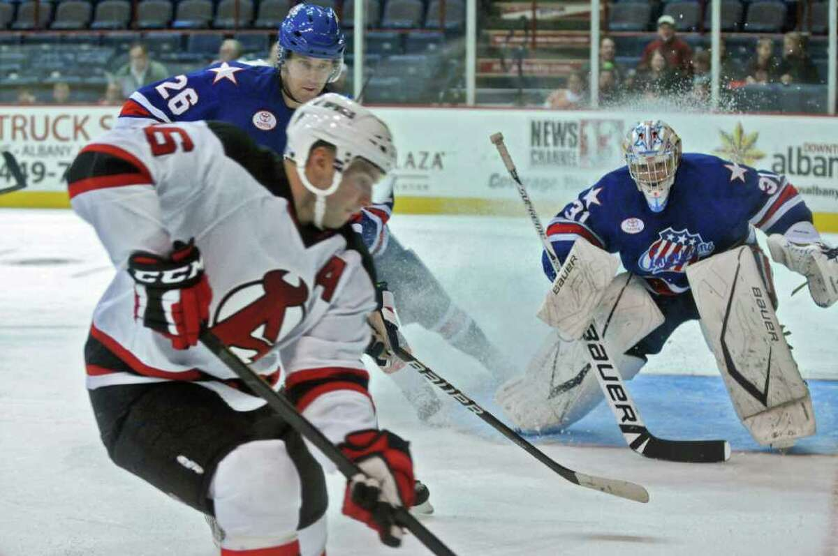 Rochester Americans goalie Drew MacIntyre, right watches as teammate Shaone Morrisonn, center, pursues Albany Devils player Chad Wiseman, left, into the corner during the first period of a game at the Times Union Center on Sunday Dec. 4, 2011 in Albany, NY. (Philip Kamrass / Times Union )