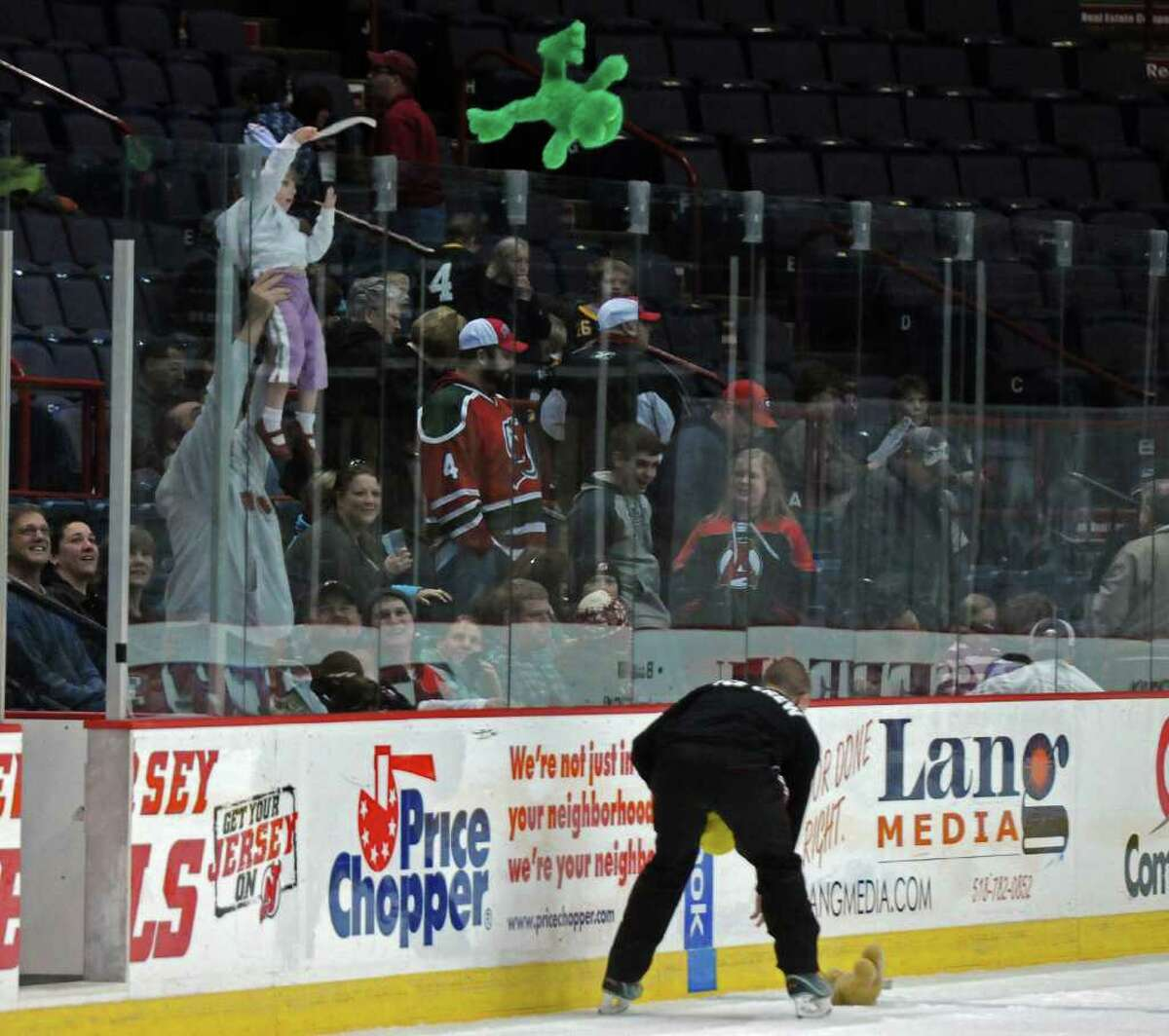 Albany Devils staff collect donated teddy bears from the ice during a