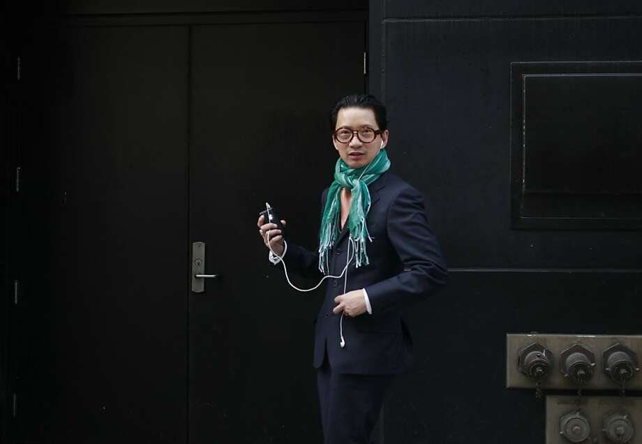 """Caught in the crosshairs of a camera, Lorence Manansala glances over as he hears the click of the shutter on his way to the Apple store on Monay Nov. 28, 2011 in San Francisco, Calif. """"To me fashion is not about the label but rather how your wear it,"""" said Manansala who today chose to add color to an entire Salvatore Ferragamo ensemble with an aqua marine colored scare he bought from a street vendor on the streets of New York. Also not to missed of course where his 'signature look' glasses made by Thierry Lasry, Cartier watch and collection of vintage diamond and white gold  rings. """"enhance with color and be yourself,"""" said Manansala. Photo: Mike Kepka, The Chronicle"""