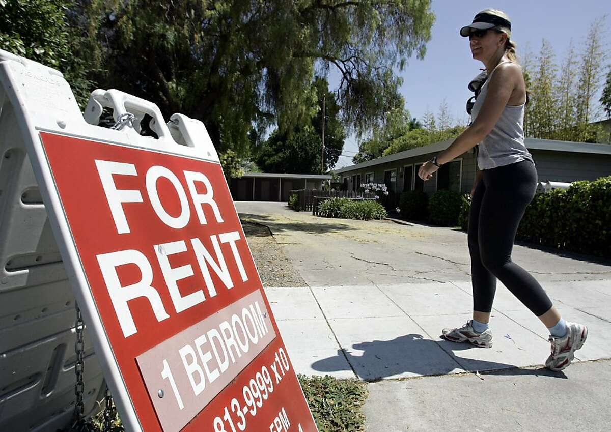 """A woman walks next to a """"For Rent"""" sign in Palo Alto Calif., Wednesday, July 19, 2006."""