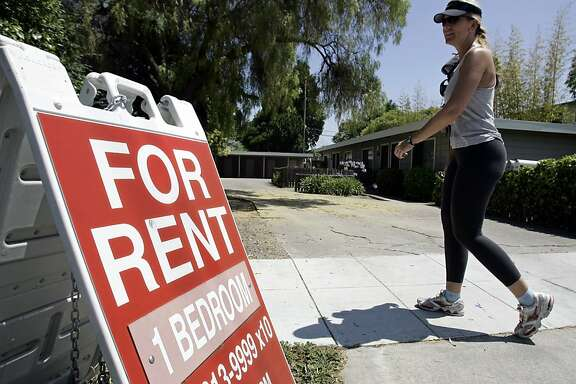 "A woman walks next to a ""For Rent"" sign  in Palo Alto Calif., Wednesday, July 19, 2006."