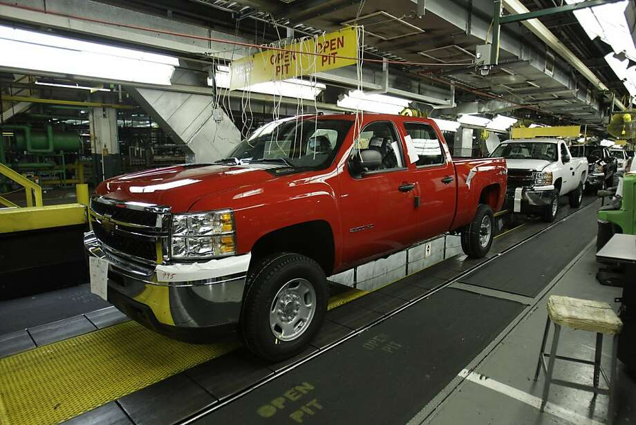 This Jan. 24, 2011 photo, shows the 2011 Chevrolet Silverado and GMC Sierra heavy-duty pickups assembly line at the Flint Assembly in Flint, Mich. GM reported Thursday, Dec. 1, 2011, strong sales of small cars as well as pickup trucks. The Chevrolet Cruze compact saw a 54 percent increase, while the Chevrolet Silverado pickup, GM's top-selling vehicle, was up 34 percent.  (AP Photo/Carlos Osorio)  Ran on: 12-02-2011 Demand for F-Series and Silverado pickups helped Ford and GM post sales gains in November. Photo: Carlos Osorio, AP