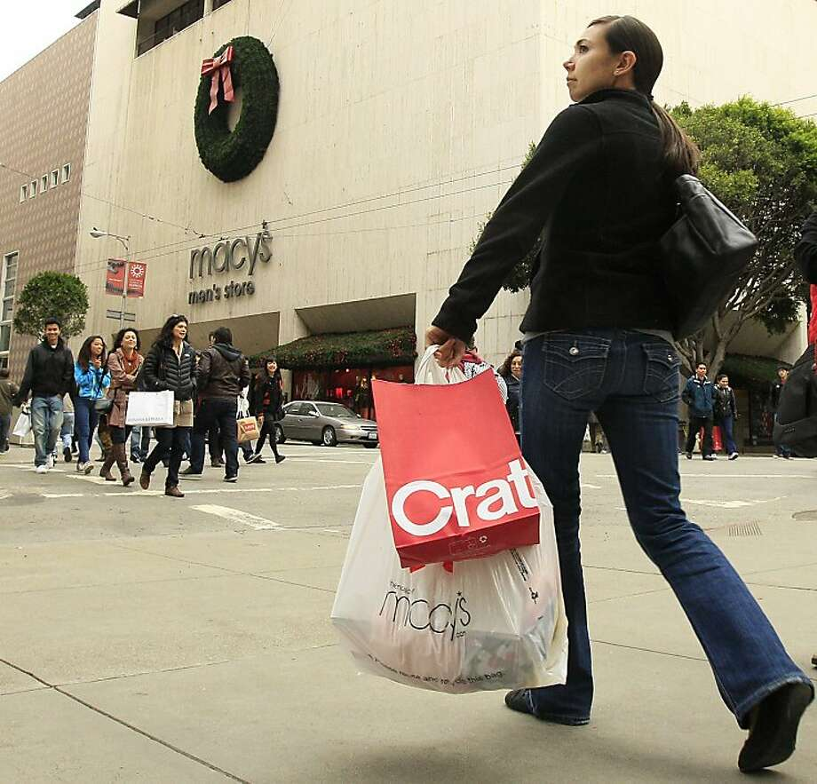 A woman carries shopping bags as she walks near a Macy's store near Union Square in San Francisco, Friday, Nov. 25, 2011. Early signs point to bigger crowds at the nation's malls and stores as retailers like Macy's and Target opened their doors at midnight. Toys R Us and a few stores other stores that opened on Thanksgiving Day also were filled with shoppers.(AP Photo/Jeff Chiu)  Ran on: 12-02-2011 A shopper laden with purchases walks near Macy's just off Union Square in S.F. on Black Friday. Photo: Jeff Chiu, AP