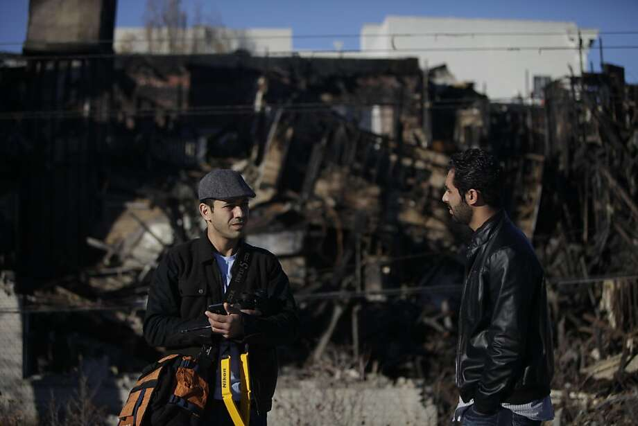Milad Yazdanpanah (l to r) and Hooman Shahrokhi talk while taking photos of the building they lived in from a roof top across the street on Wednesday, November 30, 2011 in Berkeley, Calif.  Yazdanpanah and Shahrokhi lived in the building on the corner of Telegraph  Avenue and Haste Street which burned in a five alarm fire on November 18.  They had heard a rumor that the building demolition might be in violation of what was agreed upon with the city of Berkeley and went to check it out. Photo: Lea Suzuki, The Chronicle