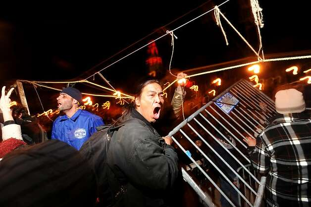 Occupy SF protesters remove police barricades fronting their camp as officers watch on Thursday, Dec. 1, 2011, in San Francisco. Police officers, who had  installed the barriers several hours early, retreated following the confrontation. Photo: Noah Berger, Special To The Chronicle