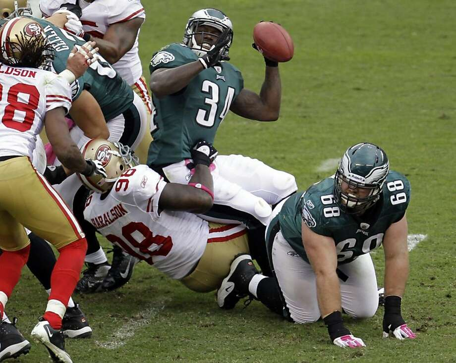 Philadelphia Eagles running back Ronnie Brown fumbles the ball as he is tackled by San Francisco 49ers outside linebacker Parys Haralson (98) in the first half of an NFL football game Sunday, Oct. 2, 2011 in Philadelphia. San Francisco recovered the fumble. (AP Photo/Julio Cortez)  Ran on: 12-02-2011 Ronnie Brown's bizarre throw may have been some strange attempt to solve the 49ers' goal-line defense. Photo: Julio Cortez, ASSOCIATED PRESS
