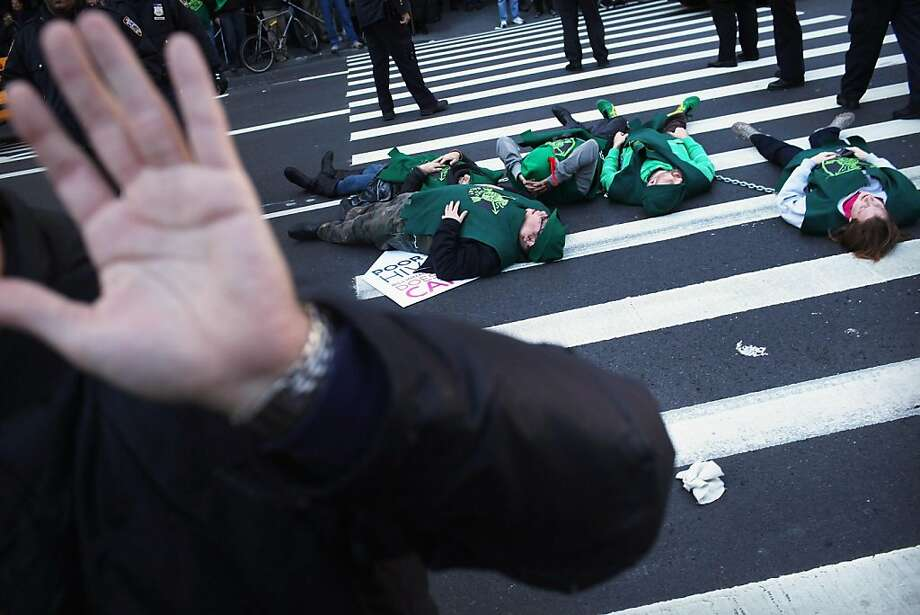 NEW YORK, NY - DECEMBER 01: AIDS protesters lie down in the street after marching up Broadway from Zuccotti Park on World AIDS Day on December 1, 2011 in New York City. About a half-dozen protesters, part of a larger group of over 100, were arrested after refusing to move while calling for Mayor Michael Bloomberg and members of Congress to tax Wall Street trade to raise money for AIDS treatment.  (Photo by Spencer Platt/Getty Images) Photo: Spencer Platt, Getty Images
