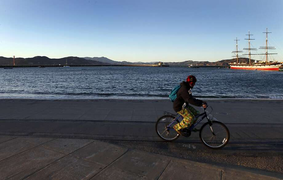 A visitor bikes past San Francisco's Aquatic Park that offers a big view Thursday December 1, 2011.The final environmental analysis for the America?s Cup regatta in 2013 will be released Thursday. One item to come out of this is clarification where swimmers, rowers and kayakers will be allowed. Photo: Lance Iversen, The Chronicle