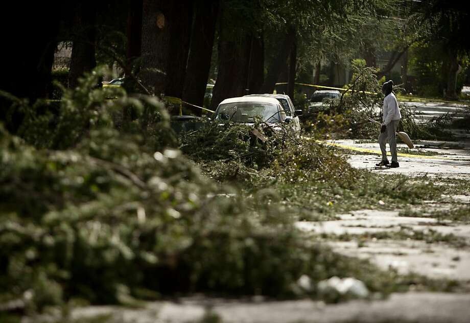 J.W. Young cleans up fallen branches caused by the Santa Ana winds on Santa Rosa Avenue, Thursday, Dec. 1, 2011, in Pasadena, Calif. Some of the fiercest winds in years slam California and move across the West, with gusts near 100 mph flipping trees and trucks, snarling air traffic and knocking out power to hundreds of thousands. (AP Photo/Bret Hartman) Photo: Bret Hartman, AP