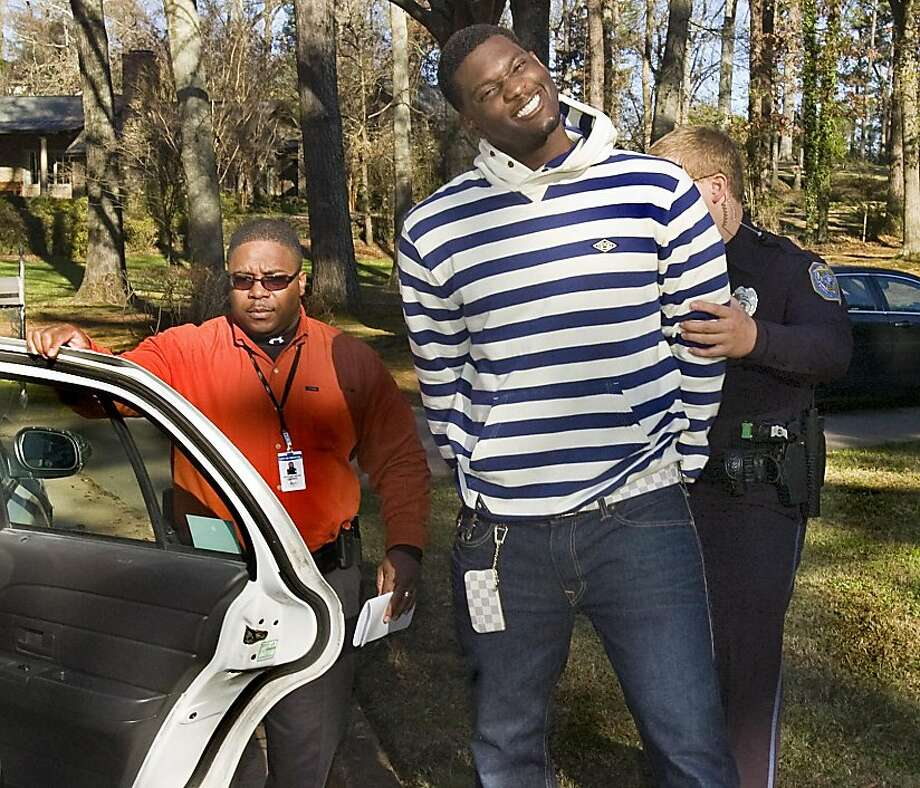 Oakland Raiders football player Rolando McClain smiles for the camera after he was arrested and handcuffed by Decatur (Ala) Police captain Nadis Carlisle, left, and officer Kirk Hamilton , Thursday afternoon, Dec. 1, 2011. McClain was arrested and charged with assault in the third degree, menacing, reckless endangerment and discharging a firearm inside the city limits in an incident that took place late Wednesday night, Nov. 30, 2011, in his hometown of Decatur.  (AP Photo/The Decatur Daily, John Godbey)   Ran on: 12-02-2011 The Raiders' Rolando McClain smiles for the camera Thursday as he is arrested for an incident Wednesday. Ran on: 12-02-2011 The Raiders' Rolando McClain smiles for the camera Thursday as he is arrested for an incident Wednesday. Ran on: 12-05-2011 Rolando McClain mugged for the cameras after his arrest in Alabama. Photo: John Godbey, AP