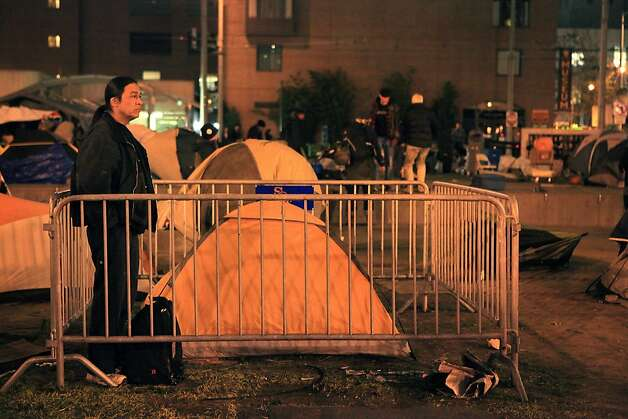 A camper at the Occupy SF keeps watch over a friends tent at Justin Herman Plaza on Thursday, December 1, 2011 in San Francisco, Calif.  SFPD Deputy Chief of Operations Kevin Cashman said that barricades along 3 sides of the camp had been set up to create a safety zone.  Protesters had removed the barricades and moved them into the camp.  The man, who gave his name as Peace Giver, had placed them around the tent with other protesters. Photo: Lea Suzuki, The Chronicle