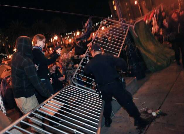Protesters at the Occupy SF camp pull barricades along Steuart Street down while a police officer tries to keep the barricade line intact at Justin Herman Plaza on Thursday, December 1, 2011 in San Francisco, Calif. Photo: Lea Suzuki, The Chronicle