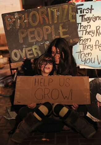 A mother and daughter sing with other protesters at the Occupy SF camp at Justin Herman Plaza on Thursday, December 1, 2011 in San Francisco, Calif. Photo: Lea Suzuki, The Chronicle