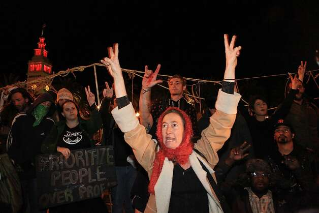 Christina Healy makes peace signs shortly after protesters removed barricades along Steuart Street at the Occupy SF camp at Justin Herman Plaza on Thursday, December 1, 2011 in San Francisco, Calif. Healy said she came down to keep the peace. Photo: Lea Suzuki, The Chronicle