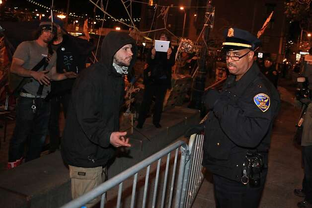 A protester argues with a police officer demanding that barricades on Steuart Street along the Occupy SF camp at Justin Herman Plaza be removed on Thursday, December 1, 2011 in San Francisco, Calif. SFPD Deputy Chief of Operations Kevin Cashman said that barricades along 3 sides of the camp had been set up to create a safety zone. Photo: Lea Suzuki, The Chronicle