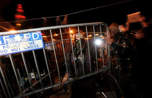 An Occupy SF protester removes police barricades fronting their camp as officers watch on Thursday, Dec. 1, 2011, in San Francisco. Police officers, who had  installed the barriers several hours early, retreated following the confrontation. Photo: Noah Berger, Special To The Chronicle