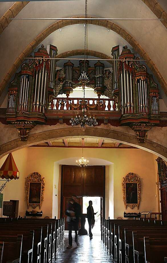 A view of the organ pipes above the entrance at the Carmel Mission in Carmel, Calif., as tourists Sebastien d'Ornano carries his daughter Chiara d'Ornano with his wife Linda d'Ornano (middle), visiting from France, on Monday, October 24, 2011. Photo: Liz Hafalia, The Chronicle