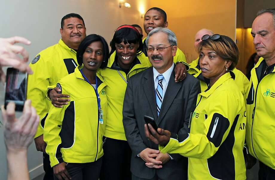 Mayor Ed Lee poses for photos with his new community ambassadors during a tour along Market Street were the ambassadors will be working Thursday December 1, 2011. Photo: Lance Iversen, The Chronicle