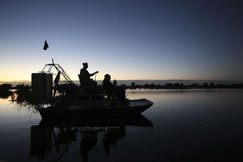 In this Nov. 28, 2011 photo, wildlife biologists on an airboat head out  on a cooling canal adjacent to the Turkey Point Nuclear Power Plant during a nighttime crocodile survey in Homestead, Fla. The crocodile monitoring program began in 1978, a year after employees stumbled upon a crocodile nest in the plantÕs cooling canal system. The initial goal was to ensure that the plant did no harm to the species but over the last three decades it has helped raise the number of crocodiles to more than 1,500 today. It is now classified as threatened, a small step toward the specieÕs survival. (AP Photo/Wilfredo Lee) Photo: Wilfredo Lee, AP