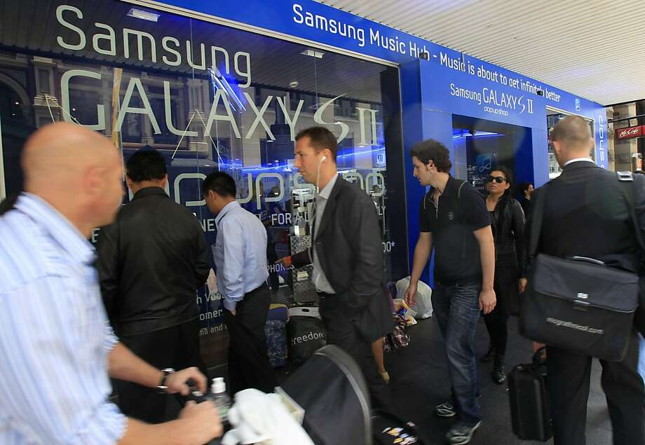 FILE - In this Oct. 13, 2011 file photo, people walk by a Samsung store in Sydney. Samsung Electronics Co. is closer to selling its new Galaxy tablet computer in Australia after a court on Wednesday, Nov. 30, overturned a ruling that favored Apple's allegations Samsung had copied its iPad and iPhone. (AP Photo/Rick Rycroft, File)  Ran on: 12-03-2011 Samsung Electronics, in a patent fight with Apple, wants to sell its new Galaxy tablet in Australia. Photo: Rick Rycroft, AP