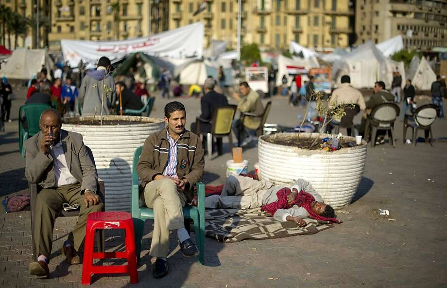 Two men sip tea as they visit a makeshift cafe at Tahrir square in Cairo on December 3, 2011. Protestors have started leaving the square with only a few hardliners boosted by day tourists still occupying their tents overnight.  AFP PHOTO / ODD ANDERSEN (Photo credit should read ODD ANDERSEN/AFP/Getty Images) Photo: Odd Andersen, AFP/Getty Images