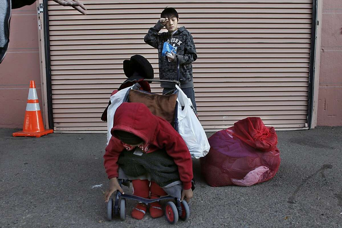 10-year-old Rudy waits with his 3-year-old brother Danny for the storage lockers to open so his family can stow away their bag of posessions for the day since they can't leave anything at the shelter they are staying at. Sophom