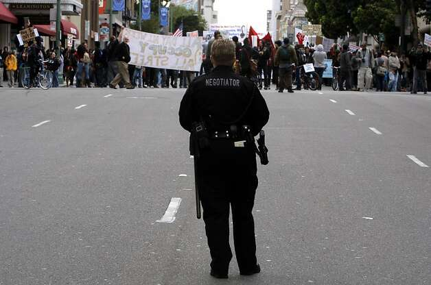 An Oakland police negotiator observes a protest march as it moves through downtown, during a Day of Action by the Occupy Oakland group on Saturday November 19, 2011 in Oakland, Ca. Photo: Michael Macor, The Chronicle