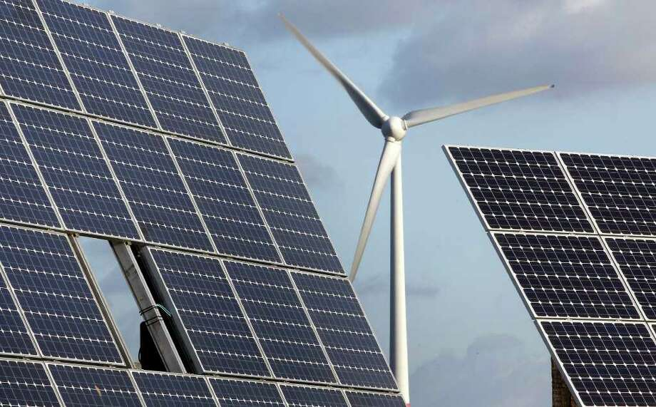 Photovoltaic modules and a windmill of a wind farm are depicted here. Photo: Michael Sohn, Associated Press / AP