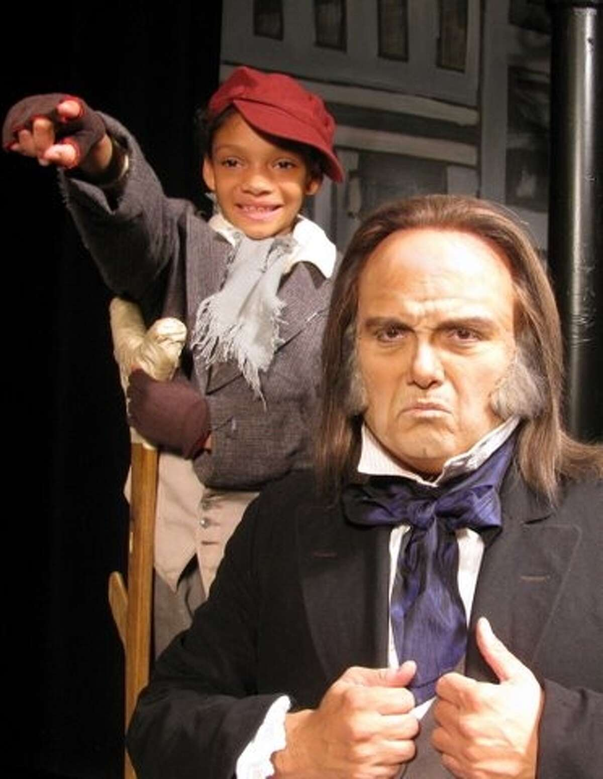 Daniela Landa-Gonzalez (from left) plays Tiny Tim and Gregroy Hinojosa plays Scrooge in