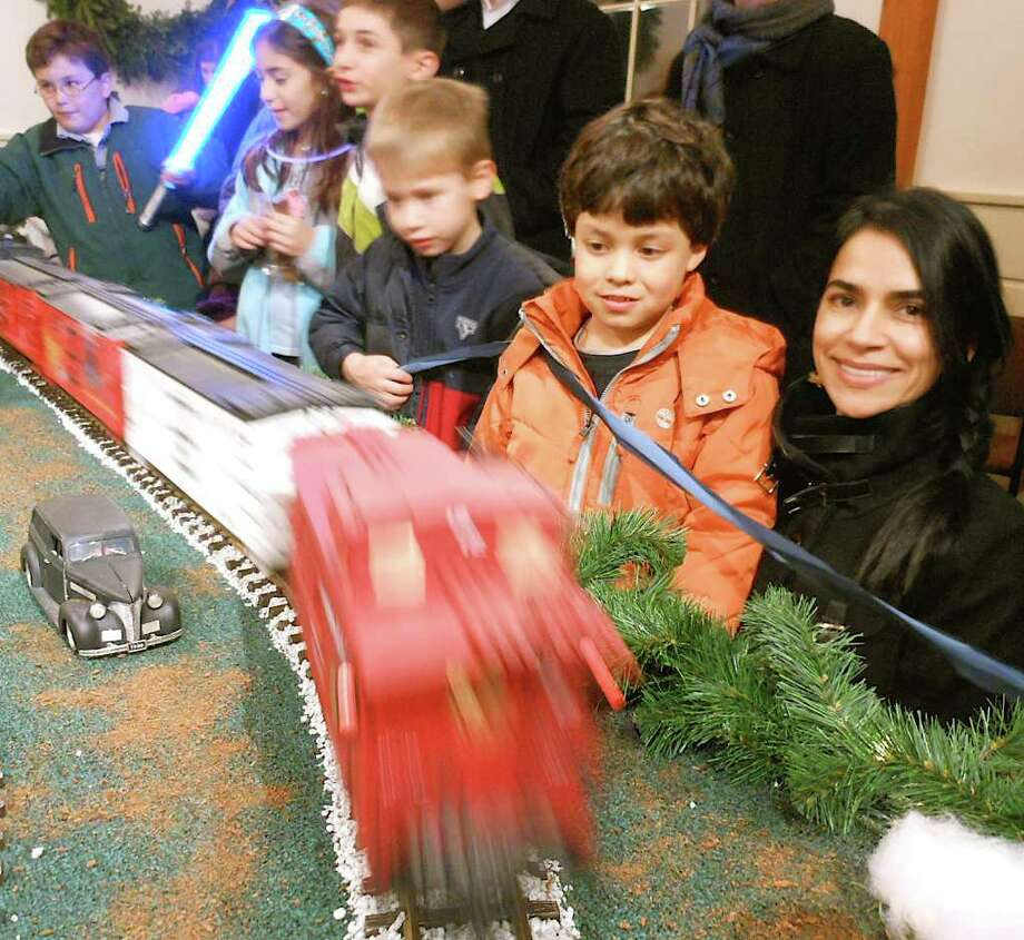 Diana Cadan and her son, Mateo, of Fairfield, foreground, enjoy the Holiday Express Train Show at the Fairfield Museum and History Center when it was unveiled for the season Friday. Photo: Mike Lauterborn / Fairfield Citizen contributed