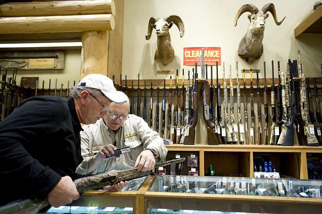 Randy Miller, left, of Cleveland, Tenn., examines a Remington shotgun with Bob Cabral, a salesman at Cabela's sporting good store in Scarborough, Maine, Oct. 27, 2011. In the last few years, many of the top names in rifles and shotguns have been acquired by the Freedom Group, a private company considered to be the most powerful force in the American commercial gun industry today. (Gretchen Ertl/The New York Times) -- PHOTOS MOVED IN ADVANCE AND NOT FOR USE - ONLINE OR IN PRINT - BEFORE NOV. 27, 2011.   Ran on: 12-04-2011 Randy Miller examines a Remington shotgun with salesman Bob Cabral at Cabela's sporting goods store in Scarborough, Maine. Photo: Gretchen Ertl, The New York Times