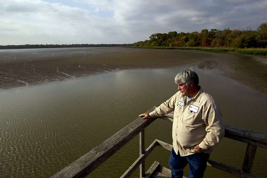 This Nov. 16, 2011, photo, Keith Tilley, the City of Groesbeck's director of public works, looks out onto the dried out 700-acre Fort Parker Lake, one of the sources of water that feeds the Navasota River, the city's main water source, in Groesbeck, Texas. The 6,000 residents of Groesbeck are on the verge of running out of water since there is not enough water flowing into the Navasota River due to a drought. The city has already taken drastic steps by pumping water out of Fort Parker Lake and is now pumping water from a quarry into a creek that runs into the Navasota river to supply the community with water. With out any steps taken the city may had been out of water by the first week of December. (AP Photo/Houston Chronicle, Johnny Hanson)  Ran on: 12-04-2011 Keith Tilley, Groesbeck's director of public works, looks out onto Fort Parker Lake, a former reservoir that is now just a series of mud banks and puddles. Photo: Johnny Hanson, AP