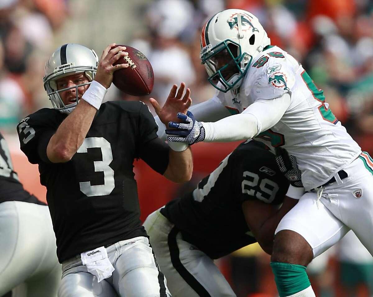 Miami Dolphins inside linebacker Kevin Burnett (56) sacks Oakland Raiders quarterback Carson Palmer (3) during the first half of an NFL football game on Sunday, Dec. 4, 2011, in Miami , Fla. (AP Photo/Wilfredo Lee)