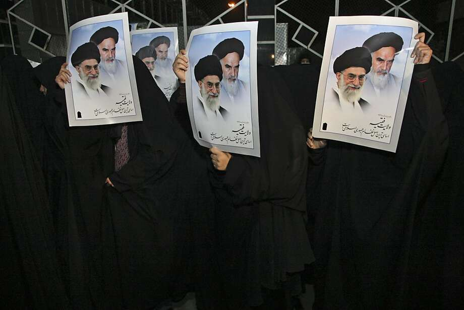 Head-to-toe veiled Iranian female students hold posters showing supreme leader Ayatollah Ali Khamenei, left in the posters, and late revolutionary founder Ayatollah Khomeini, during a demonstration to welcome Iranian diplomats expelled from London in retaliation for attacks on British compounds in Tehran, at the Mehrabad airport in Tehran, Iran, early Saturday, Dec. 3, 2011. About 150 hard-liners gathered at Tehran's Mehrabad airport to give the diplomats a hero's welcome but the Iranian government has reportedly opposed any high-profile welcome. Iran's official IRNA news agency says the diplomats plane landed at early Saturday morning. (AP Photo/Vahid Salemi) Photo: Vahid Salemi, AP