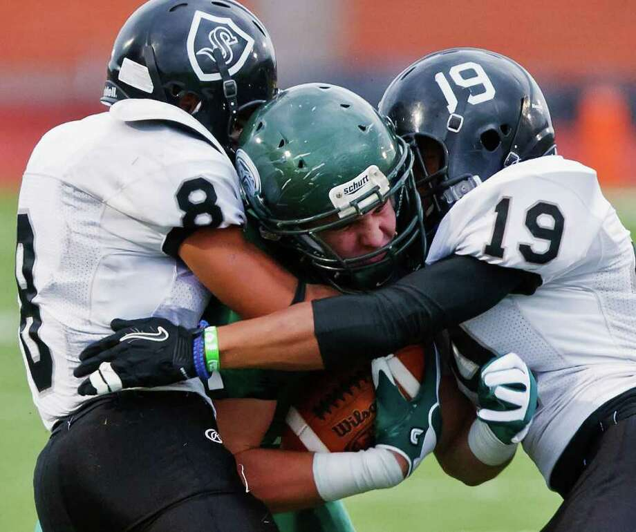 Reagan's Connor Knight is sandwiched by Steele's John burton (left) and Devere Carrington during the first quarter of their Class 5A Division II quarterfinal playoff game at Heroes Stadium on Dec. 3, 2011.  Steele advanced to the next round with a 35-10 victory over the Rattlers.  Photo by Marvin Pfeiffer Photo: MARVIN PFEIFFER, Marvin Pfeiffer/Prime Time Newspapers / Prime Time Newspapers 2011