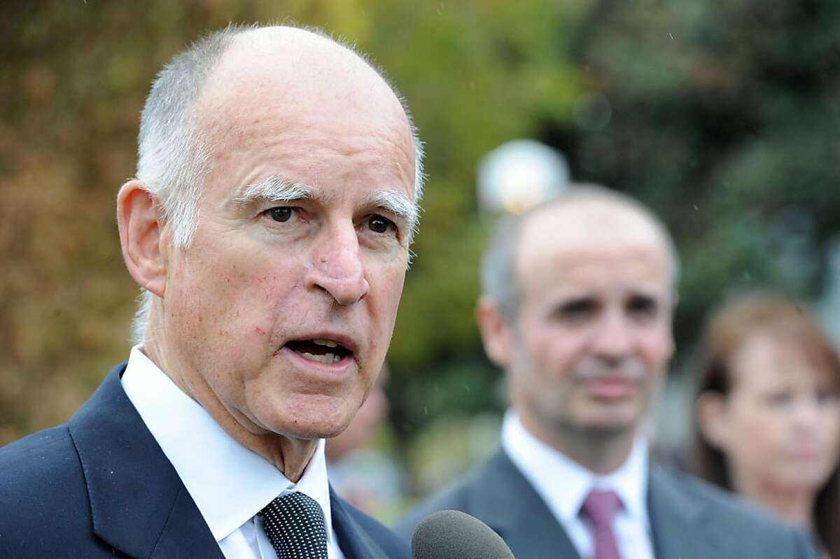 Gov. Jerry Brown speaks at a press conference while SunEdison President Carlos Domenech listens at SunEdison headquarters in Belmont on Monday, October 10, 2011. SunEdison develops large solar power projects and has transferred its headquarters from Maryland to Belmont, drawn by California's supportive political and financial environment for renewable power.
