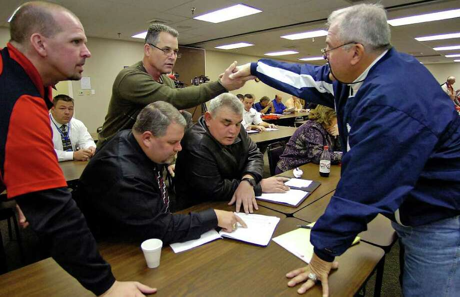 Richard Hazlewood, Superintendent of Kirbyville CISD, second from left, shakes hands with West Orange-Stark Defensive Coordinator Cornel Thompson, right, after the group had looked over the UIL  2010 District Assignments and Reclassification Information Packets.  Mike Brewster, with Kirbyville, Gary Fairchild, middle, with Kirbyville, and Jack Alvarez, right, also with Kirbyville, continue to look at the plan.     Dave Ryan/The Enterprise / Beaumont