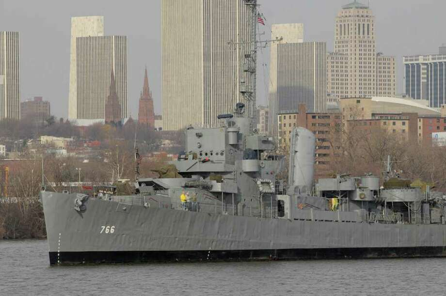 The USS Slater is pushed down the Hudson River past the Albany skyline as the World War II destroyer escort is moved across the Hudson River from the Albany side to the Rensselaer side for its winter berth.  Donjon Marine tugs and employees along with staff and volunteers from the USS Slater took part in the move on Monday, Dec. 5, 2011.   (Paul Buckowski / Times Union) Photo: Paul Buckowski / 10015666A