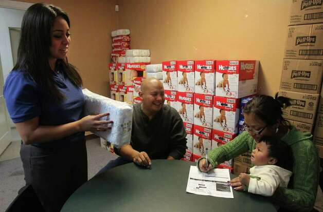 Claudia Franco gives diapers to Manuel Obaya and Hope Zuniga as she holds their 11-month-old son, Manuel, at the Hispanic Religious Partnership's Diaper Bank. Photo: SAN ANTONIO EXPRESS-NEWS