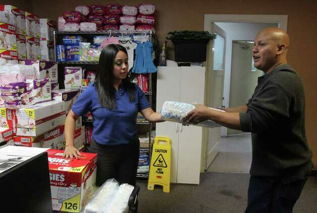 Claudia Franco gives diapers to Manuel Obaya at the Hispanic Religious Partnership's Diaper Bank. Photo: JOHN DAVENPORT, SAN ANTONIO EXPRESS-NEWS / SAN ANTONIO EXPRESS-NEWS