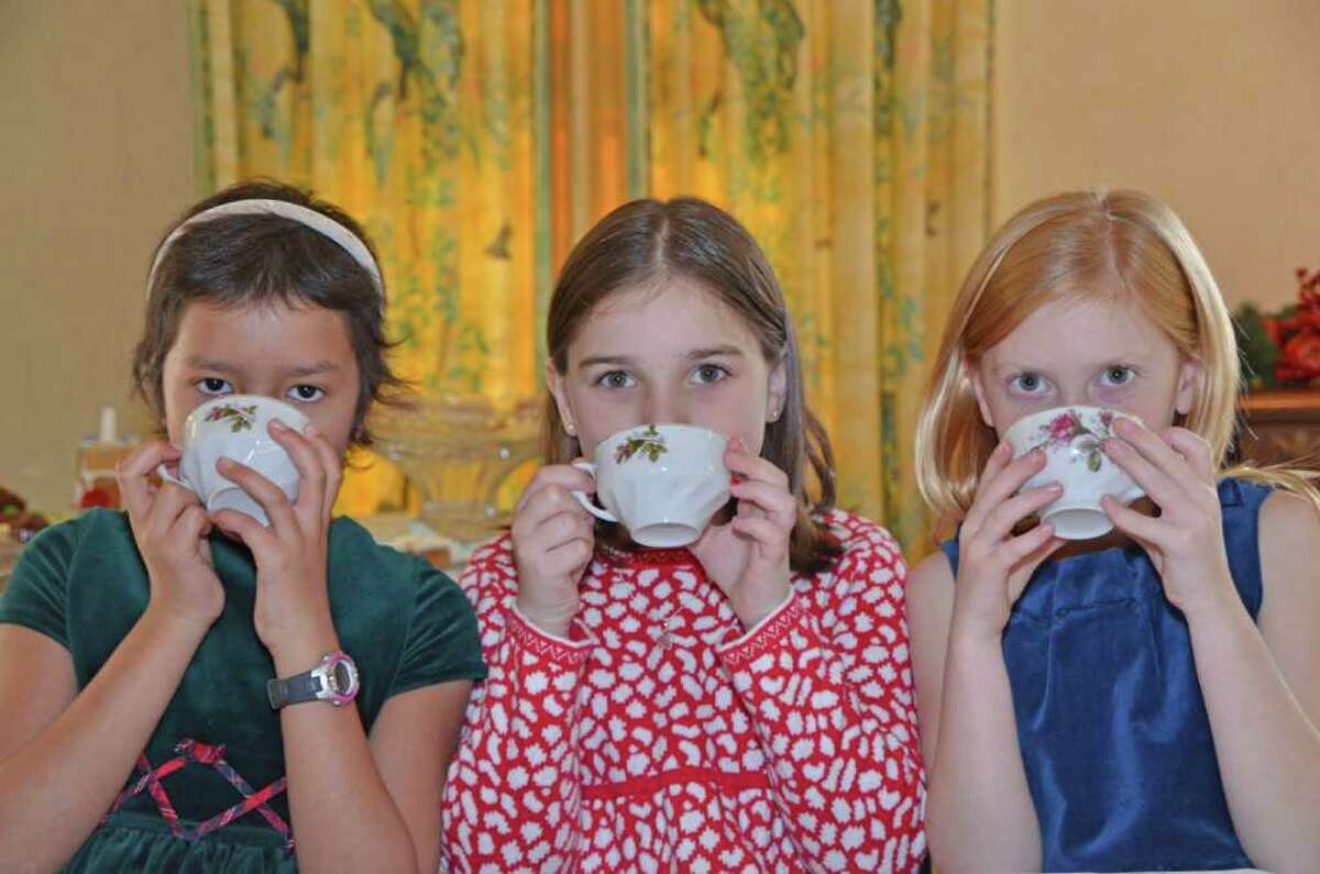 Three cups of tea, please. Ashley Ruth, Julia DiCarlo and Brynn Schmitt enjoy tea and pastries at the New Canaan Historical Society Holiday Open House last Saturday, December 3, 2011. Gingerbread houses were also on display while children decorated their own.