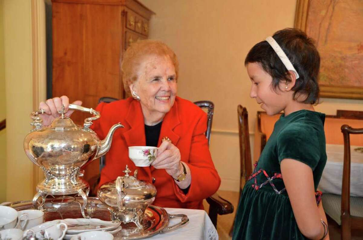 Barbara Porterfield serves tea to young Ashley Ruth at Saturday's Holiday Open House at the New Canaan Historical Society.