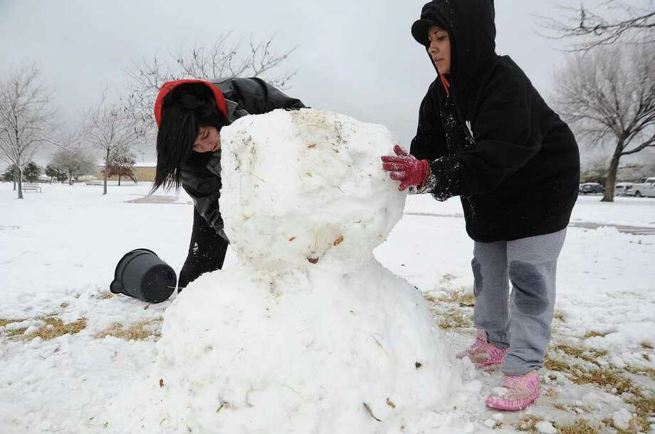 Jovonica Cortinez, left, 19, and her friend Angelina Llanez, 30, make a snowman Monday, Dec. 5, 2011, in Purple Sage Park in Odessa, Texas. The National Weather Service indicated that Odessa had received about 2.5 inches of snow but that other parts of the area had received more. (AP Photo/Odessa American, Mark Sterkel) Photo: Mark Sterkel, Associated Press