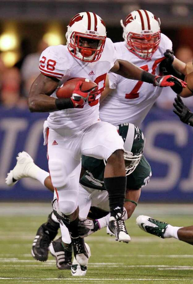 Wisconsin's Montee Ball, breaking a tackle against Michigan State in the Big Ten title game, is one TD shy of equaling Barry Sanders' NCAA career record. Photo: Michael Conroy, Associated Press