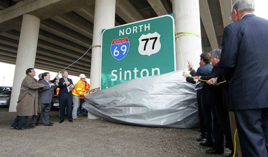 City, state and federal officials unveil a 10 foot by 10 foot highway sign marking the first segment of Interstate 69 in Texas Monday Dec 05, 2011 under the US 77 overpass in Robstown, Texas. The first segment is concurrently designated with US 77 for 6.2 miles from State High 44 in Robstown to Interstate 37 in Corpus Christi. Photo: TODD YATES/CALLER-TIMES, AP / Corpus Christi Caller-Times